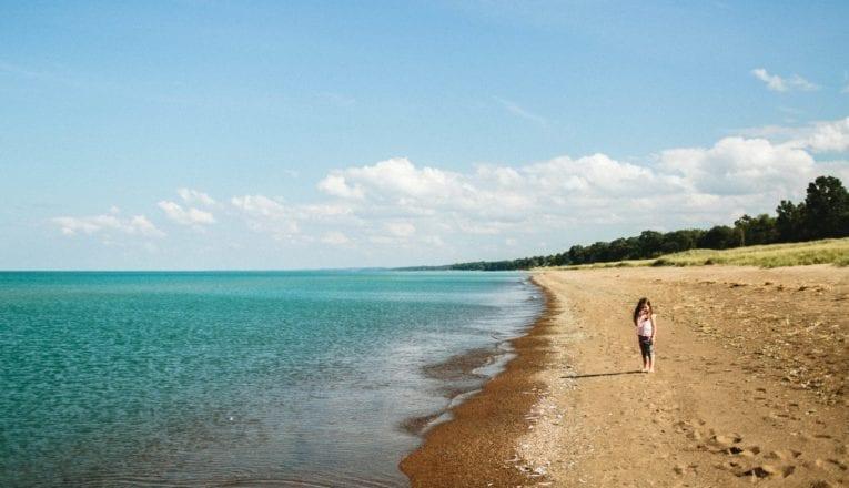 A little girl standing on an expansive Lake Michigan beach in New Buffalo, Michigan.
